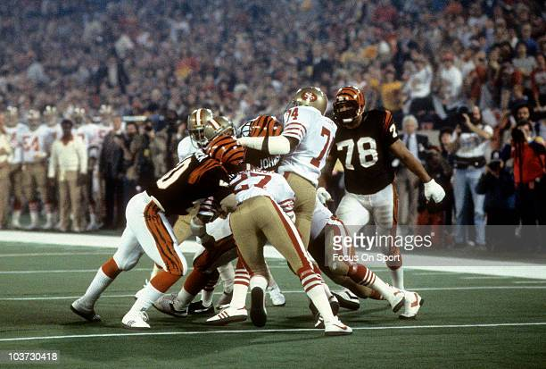 Defensive end Fred Dean and teammate Carlton Williamson of the San Francisco 49ers try to bring down running back Pete Johnson of the Cincinnati...