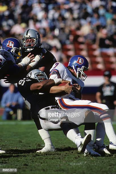Defensive end Greg Townsend of the Los Angeles Raiders tackles Quarterback John Elway of the Denver Broncos during the game at the Los Angeles...