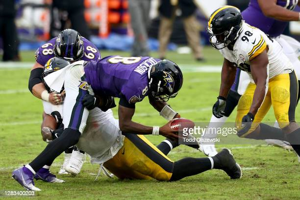 Defensive end Isaiah Buggs and inside linebacker Vince Williams of the Pittsburgh Steelers stop quarterback Lamar Jackson of the Baltimore Ravens...