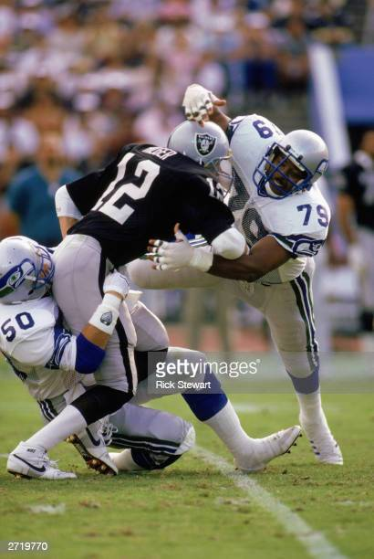 Defensive end Jacob Green of the Seattle Seahawks tackles a Los Angeles Raiders player on December 18, 1988 in the Los Angeles Coliseum in Los...