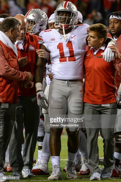 Defensive end Jalyn Holmes of the Ohio State Buckeyes is help off the field after and injury against the Nebraska Cornhuskers at Memorial Stadium on...