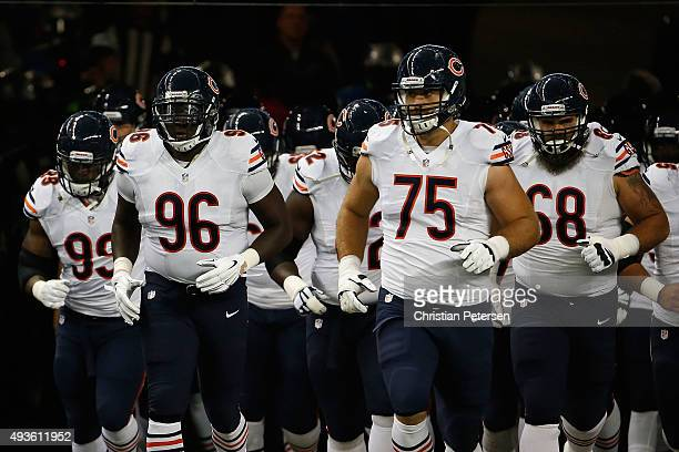 Defensive end Jarvis Jenkins and offensive tackle Kyle Long of the Chicago Bears run out onto the field before the NFL game against the Detroit Lions...