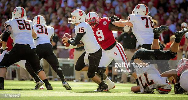 Defensive end Jason Ankrah of the Nebraska Cornhuskers fights off a block to chase down quarterback Kevin Yost of the Idaho State Bengals during...