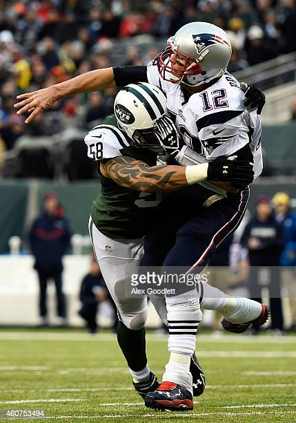 Defensive end Jason Babin of the New York Jets tackles quarterback Tom Brady of the New England Patriots during a game at MetLife Stadium on December...