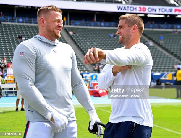 Defensive end J.J. Watt of the Houston Texans and his brother fullback Derek Watt of the Los Angeles Chargers talk on the field before the game at...