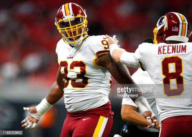 Defensive end Jonathan Allen of the Washington Redskins reacts with quarterback Case Keenum of the Washington Redskins after an Atlanta Falcons...