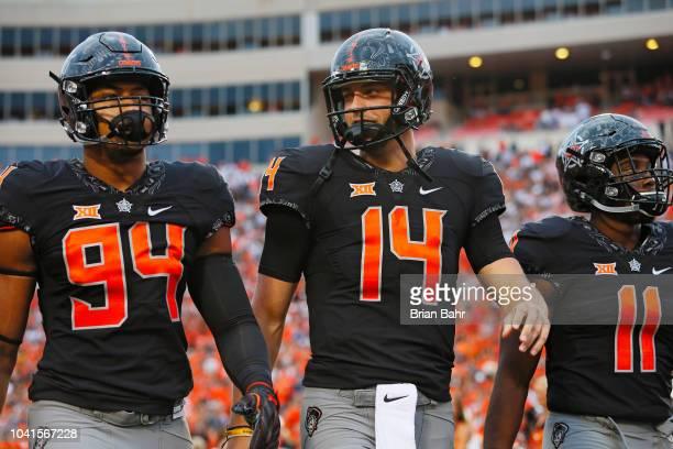 Defensive end Jordan Brailford quarterback Taylor Cornelius and linebacker Amen Ogbongbemiga of the Oklahoma State Cowboys walk onto the field for a...