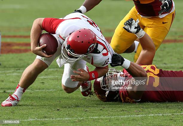 Defensive end J.R. Tavai of the USC Trojans pulls down quarterback Adam Schulz of the Utah Utes for a sack in the fourth quarter at Los Angeles...