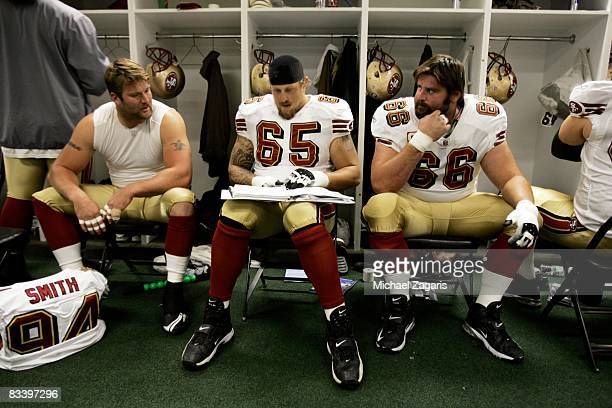 Defensive end Justin Smith tackle Barry Sims and center Eric Heitmann of the San Francisco 49ers talk in the locker room before the NFL game against...