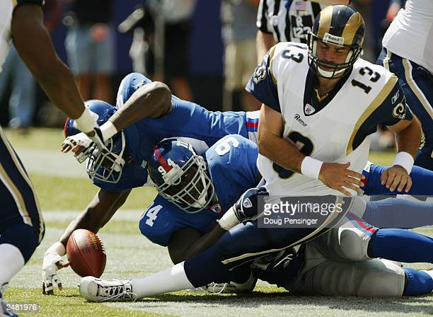 Defensive end Kenny Holmes of the New York Giants recovers a fumble in the end zone for a touchdown after he and teammate linebacker William Joseph...