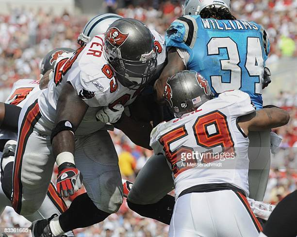 Defensive end Kevin Carter and linebacker Cato June of the Tampa Bay Buccaneers tackle running back DeAngelo Williams of the Carolina Panthers at...