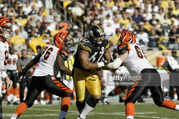 Defensive end Kimo von Oelhoffen of the Pittsburgh Steelers tries to get past offensive tackle Levi Jones and offensive guard Eric Steinbach of the...