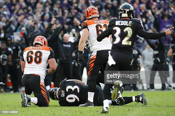 Defensive end Lawrence Guy of the Baltimore Ravens recovers a fumble while teammate strong safety Eric Weddle celebrates against guard Kevin Zeitler...