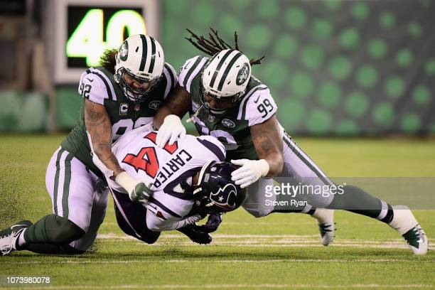 Defensive end Leonard Williams and nose tackle Steve McLendon of the New York Jets tackle wide receiver DeAndre Carter of the Houston Texans during...