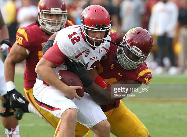 Defensive end Leonard Williams o the USC Trojans sacks quarterback Adam Schulz of the Utah Utes in the fourth quarter at Los Angeles Coliseum on...