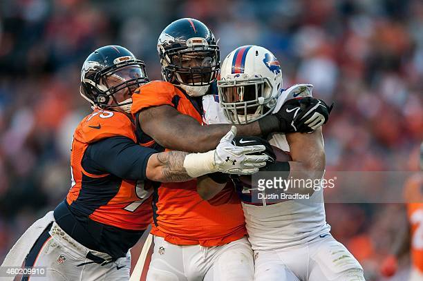 Defensive end Malik Jackson and defensive end Derek Wolfe of the Denver Broncos tackle running back Fred Jackson of the Buffalo Bills during a game...