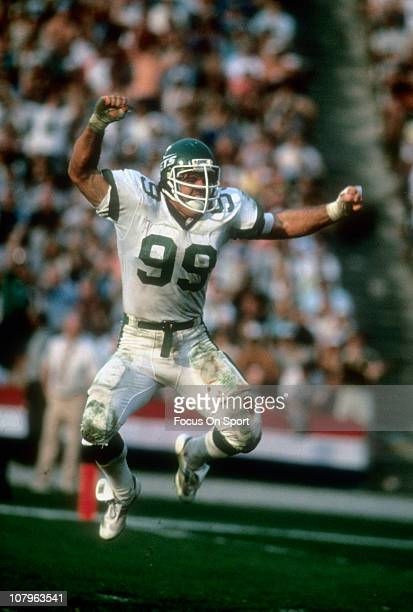 Defensive end Mark Gastineau of the New York Jets leaps in the air celebrating after making a play against the Los Angeles Raiders during an NFL/AFC...