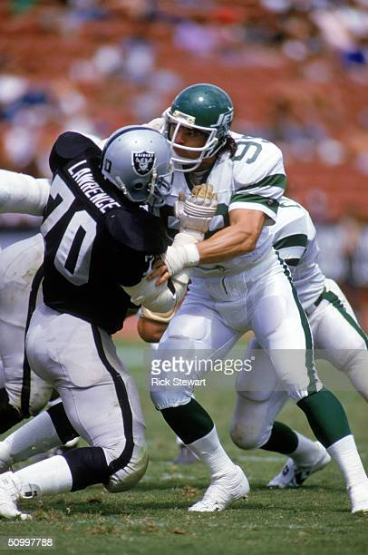 Defensive end Mark Gastineau of the New York Jets tries to get around offensive lineman Henry Lawrence of the Los Angeles Raiders during a game at...