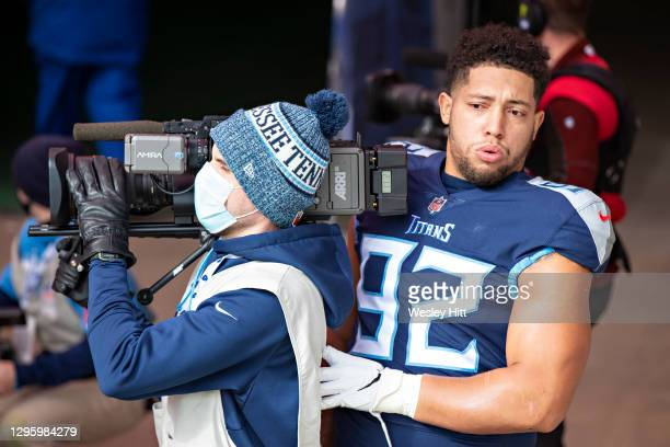 Defensive end Matt Dickerson of the Tennessee Titans is almost taken out by a cameraman before their AFC Wild Card Playoff game against the Baltimore...