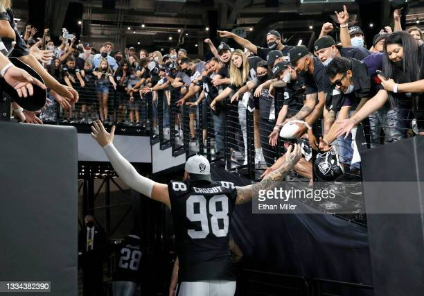Defensive end Maxx Crosby of the Las Vegas Raiders high-five fans as he runs off the field following the team's 20-7 victory over the Seattle...