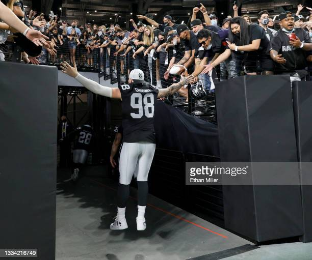 Defensive end Maxx Crosby of the Las Vegas Raiders leaps in the air to high-five fans as he runs off the field following the team's 20-7 victory over...