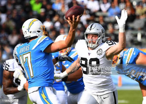 Defensive end Maxx Crosby of the Oakland Raiders pressures quarterback Philip Rivers of the Los Angeles Chargers as he throws a pass in the game at...