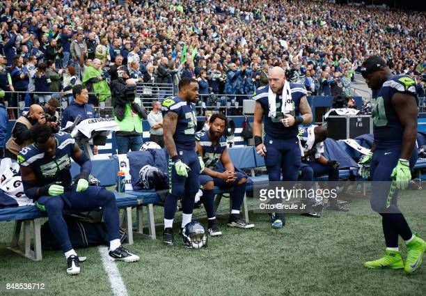 Defensive end Michael Bennett of the Seattle Seahawks center sitting is joined by teammates defensive end Frank Clark left running back Thomas Rawls...