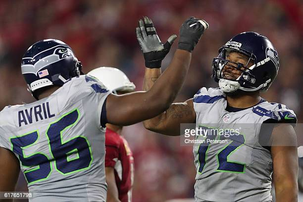 Defensive end Michael Bennett of the Seattle Seahawks high fives Cliff Avril after a defensive stop against the Arizona Cardinals during the second...