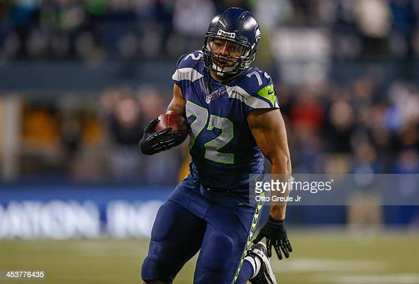 Defensive end Michael Bennett of the Seattle Seahawks runs for a touchdown after recovering a fumble against the New Orleans Saints in the first...