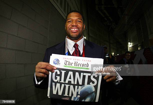 Defensive end Michael Strahan of the New York Giants holds a copy of the Bergen Record with the headline GIANTS WIN after the Giants defeated the New...