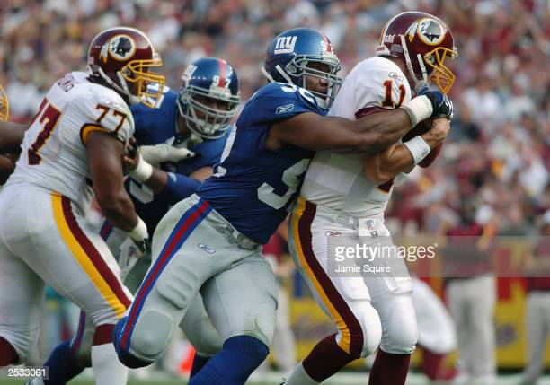 Defensive end Michael Strahan of the New York Giants sacks quarterback Patrick Ramsey of the Washington Redskins on September 21 2003 at FedEx Field...