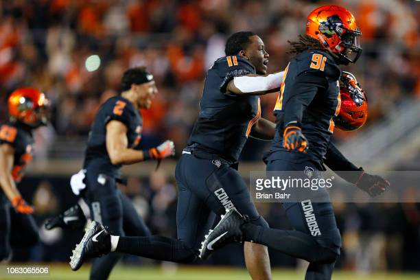 Defensive end Mike Scott linebacker Amen Ogbongbemiga and wide receiver Tylan Wallace of the Oklahoma State Cowboys celebrate a win over the West...