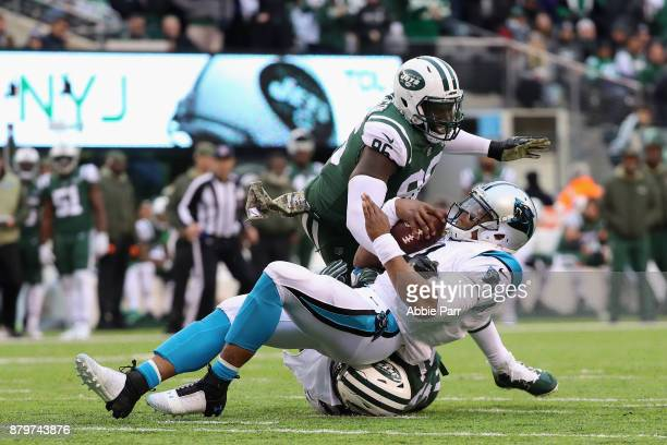 Defensive end Muhammad Wilkerson and inside linebacker Demario Davis of the New York Jets tackle quarterback Cam Newton of the Carolina Panthers...