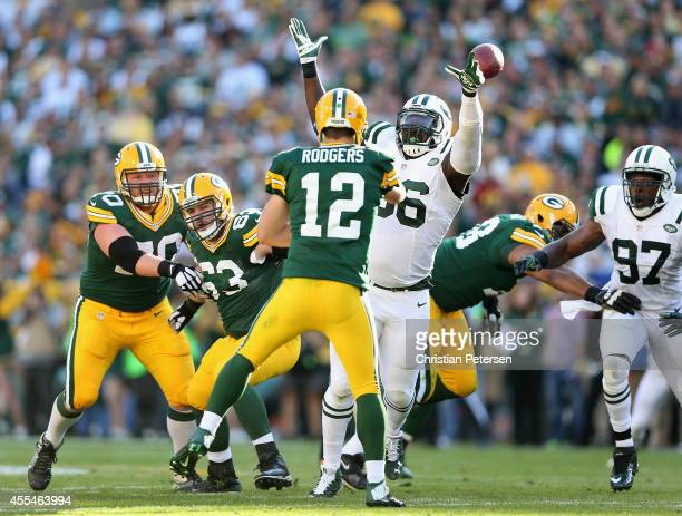 Defensive end Muhammad Wilkerson of the New York Jets attempts to block a pass thrown by quarterback Aaron Rodgers of the Green Bay Packers during...