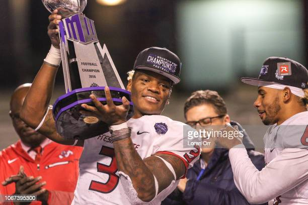 Defensive end Mykal Walker of the Fresno State Bulldogs defensive player of the game holds up the championship trophy following the conclusion of the...
