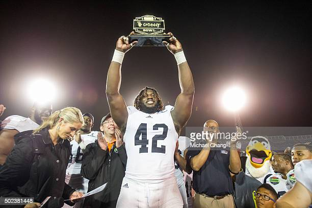 Defensive end Nardo Govan of the Georgia Southern Eagles hold up the Most Valuable Defensive trophy after defeating the Bowling Green Falcons on...