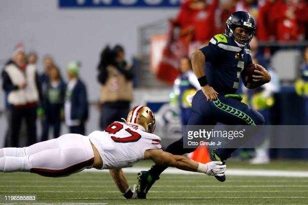Defensive end Nick Bosa of the San Francisco 49ers dives to tackle quarterback Russell Wilson of the Seattle Seahawks during the game at CenturyLink...
