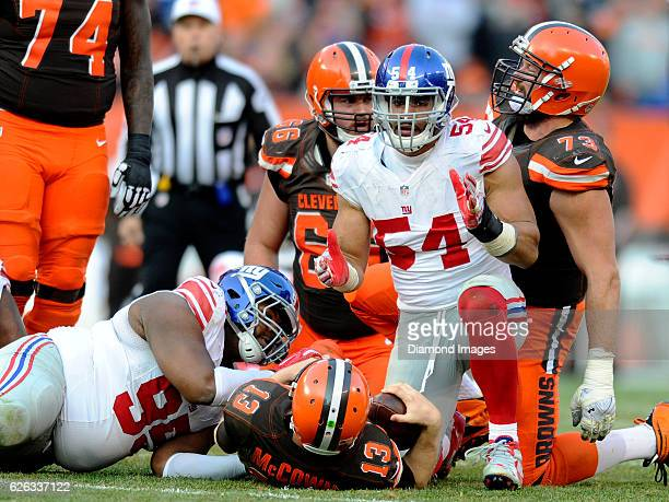 Defensive end Olivier Vernon of the New York Giants kneels over quarterback Josh McCown of the Cleveland Browns after sacking him during a game on...