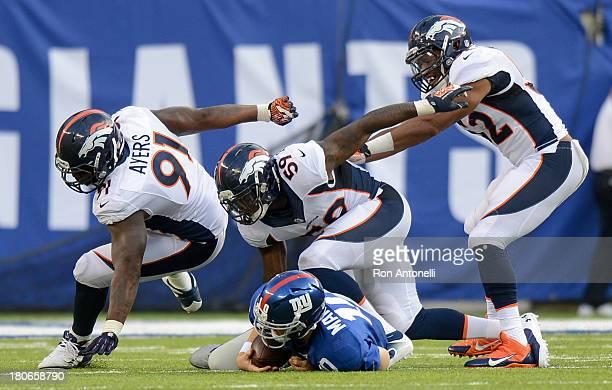 Defensive end Robert Ayers, linebacker Danny Trevathan and outside linebacker Wesley Woodyard of the Denver Broncos celebrate after quarterback Eli...