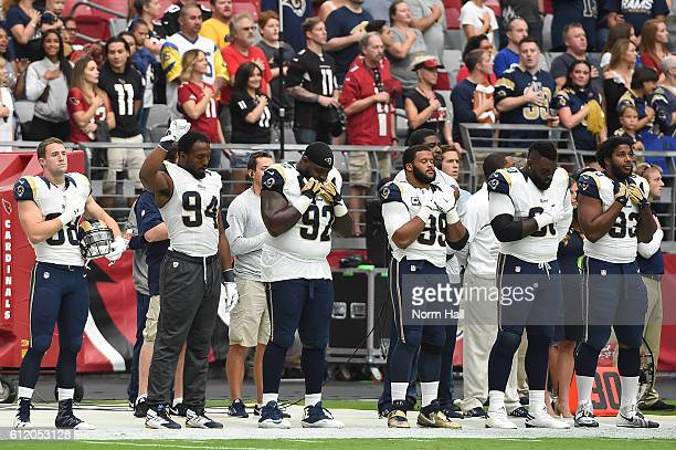 Defensive end Robert Quinn of the Los Angeles Rams holds up his fist during the national anthem prior to the NFL game against the Arizona Cardinals...