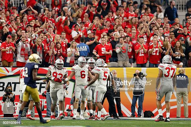 Defensive end Sam Hubbard of the Ohio State Buckeyes celebrates with Raekwon McMillan after a sack on quarterback DeShone Kizer of the Notre Dame...