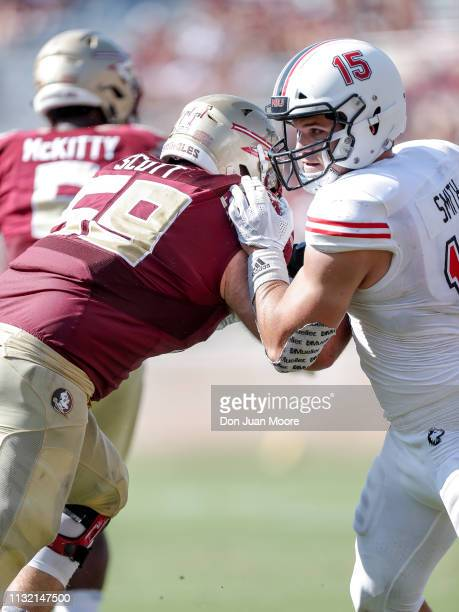 Defensive End Sutton Smith of the Northern Illinois Huskies is being blocked by Tackle Brady Scott of the Florida State Seminoles during the game at...