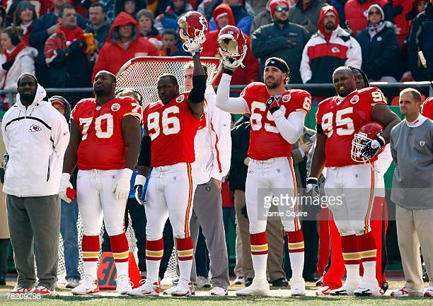 Defensive ends Jared Allen and Jimmy Wilkerson of the Kansas City Chiefs hoist their helmets during a moment of silence in honor of slain safety Sean...