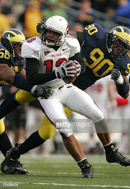 Defensive ends Tim Jamison and LaMarr Woodley of the Michigan Wolverines sack quarterback Nate Davis of the Ball State Cardinals for a loss of five...