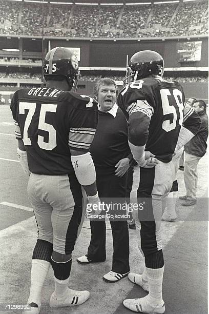 Defensive line coach George Perles center of the Pittsburgh Steelers talks with defensive lineman Joe Greene and linebacker Jack Lambert during a...