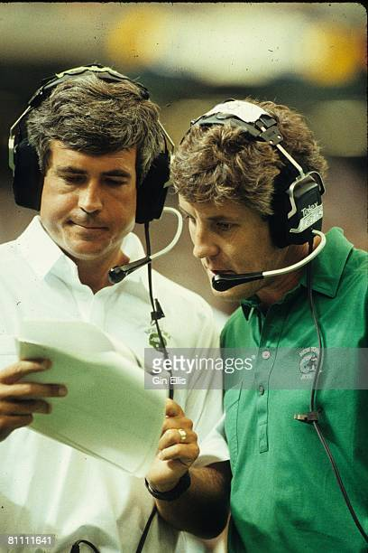 Defensive line coach Greg Robinson of the New York Jets looks over a play sheet with defensive coordinator Pete Carroll on the sideline against the...