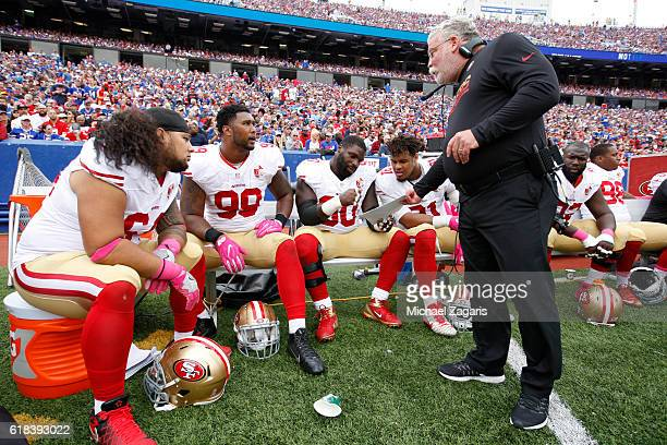 Defensive Line Coach Jerry Azzinaro of the San Francisco 49ers talks with Arik Armstead and DeForest Buckner on the sideline during the game against...