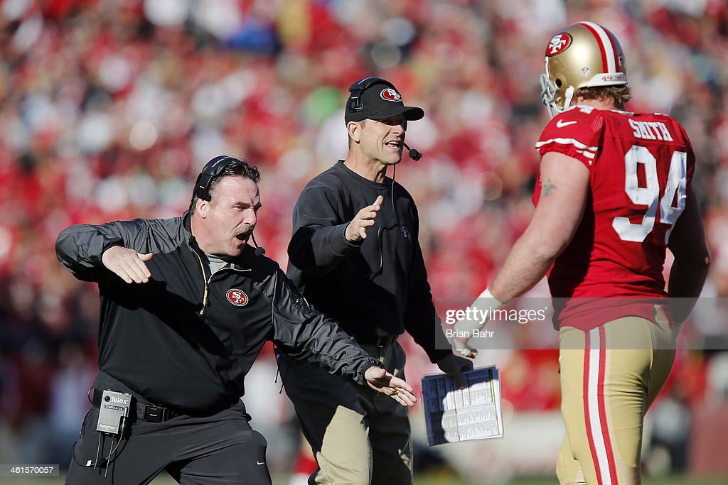 Defensive line coach Jim Tomsula and head coach Jim Harbaugh congratulate defensive tackle Justin Smith #94 of the San Francisco 49ers after a sack on quarterback Russell Wilson of the Seattle Seahawks for a loss of nine yards in the first quarter on December 8, 2013 at Candlestick Park in San Francisco, California. The 49ers won 19-17.