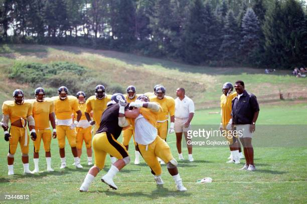 Defensive line coach Joe Greene of the Pittsburgh Steelers watches linemen during a drill at summer training camp at St Vincent College in July 1991...