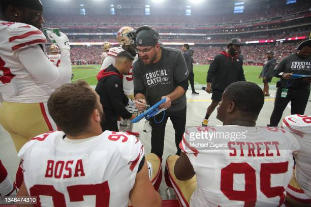 Defensive Line Coach Kris Kocurek of the San Francisco 49ers talks with Nick Bosa and Kentavius Street on the sidelines during the game against the...
